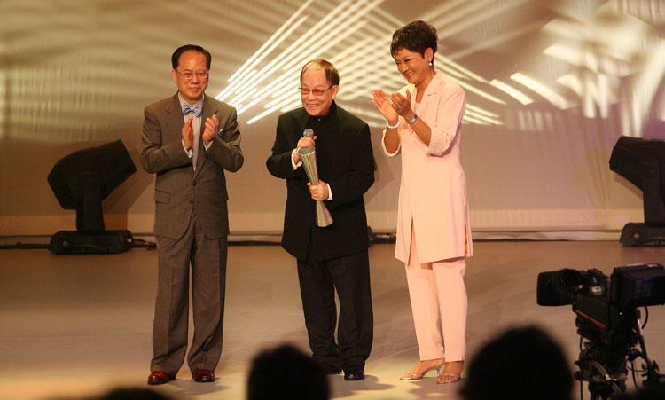 """2011年顾嘉辉(中)获""""2011香港艺术发展奖""""——「终身成就奖」,由当时的行政长官曾荫权(左)颁发。右边是著名香港歌手叶丽仪。"""